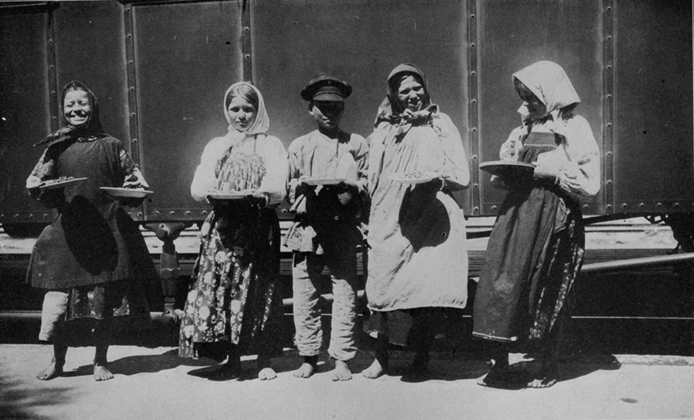 """Platform vendors selling plates of food to passengers along the Trans-Siberian route, 1900. Photograph by Michael Ward. From E. Burton Holmes, """"The Burton Holmes Lectures, Vol. VIII"""" (1901)."""