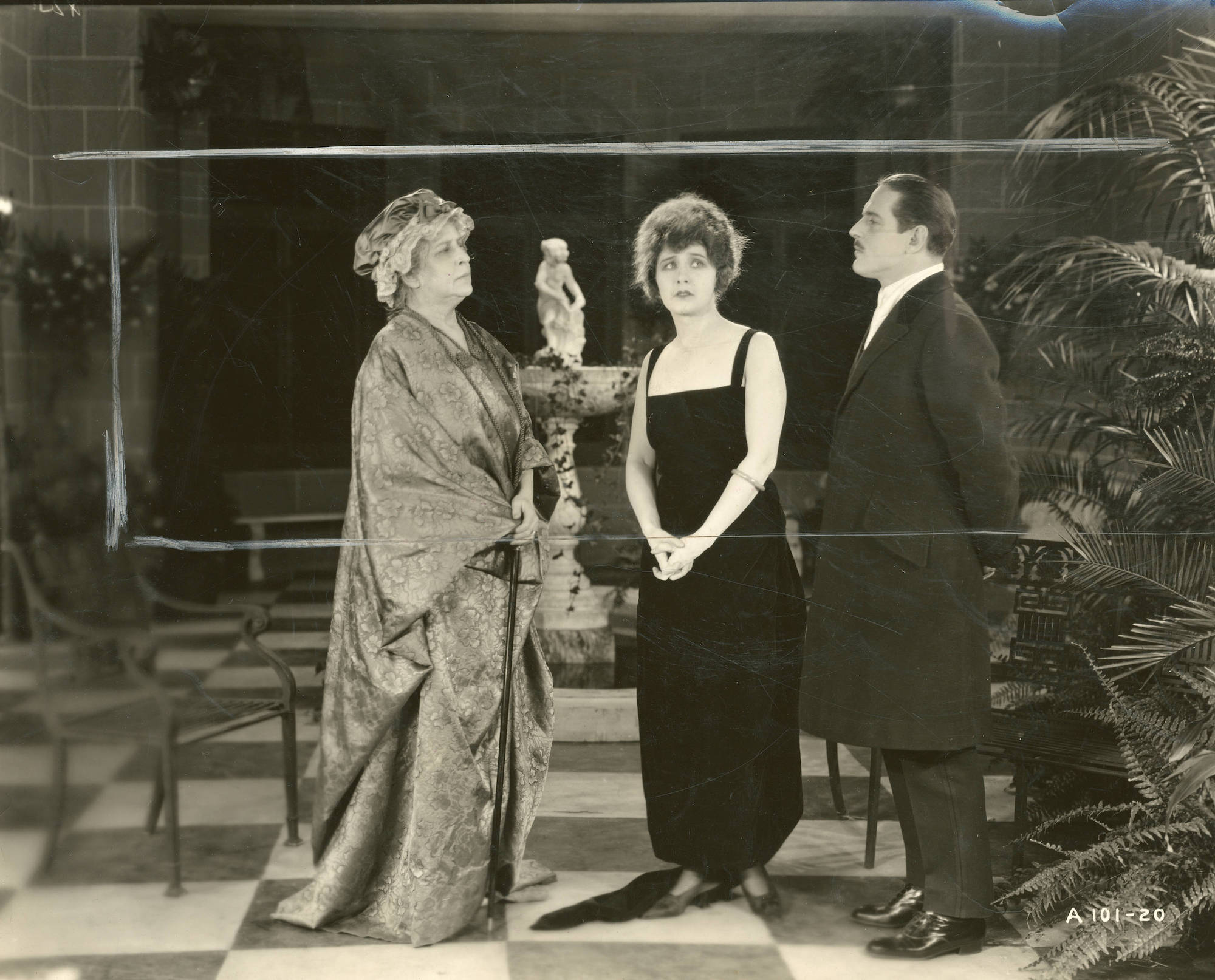 A black and white photograph of a man and two women standing in a courtyard. The man and older woman look at each other sternly, while the younger woman stands between them looking concerned.