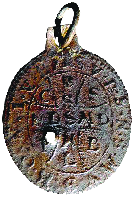 A circular metal amulet embossed with a cross and letters