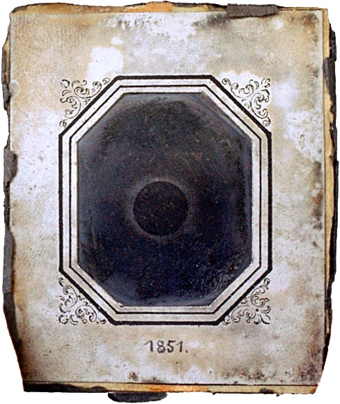 A small black-and-white image of a solar eclipse in a white paper frame. On the frame, someone has written 1851.
