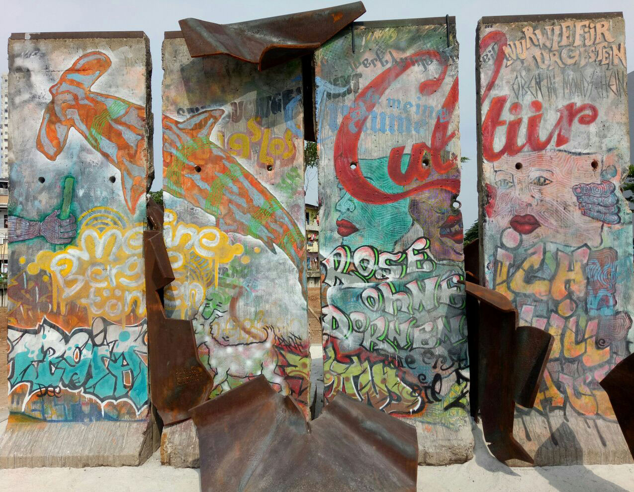 Four segments of the Berlin Wall covered in colourful paintings and adorned with metal figures, climbing over the wall and slipping through the spaces between the segments.