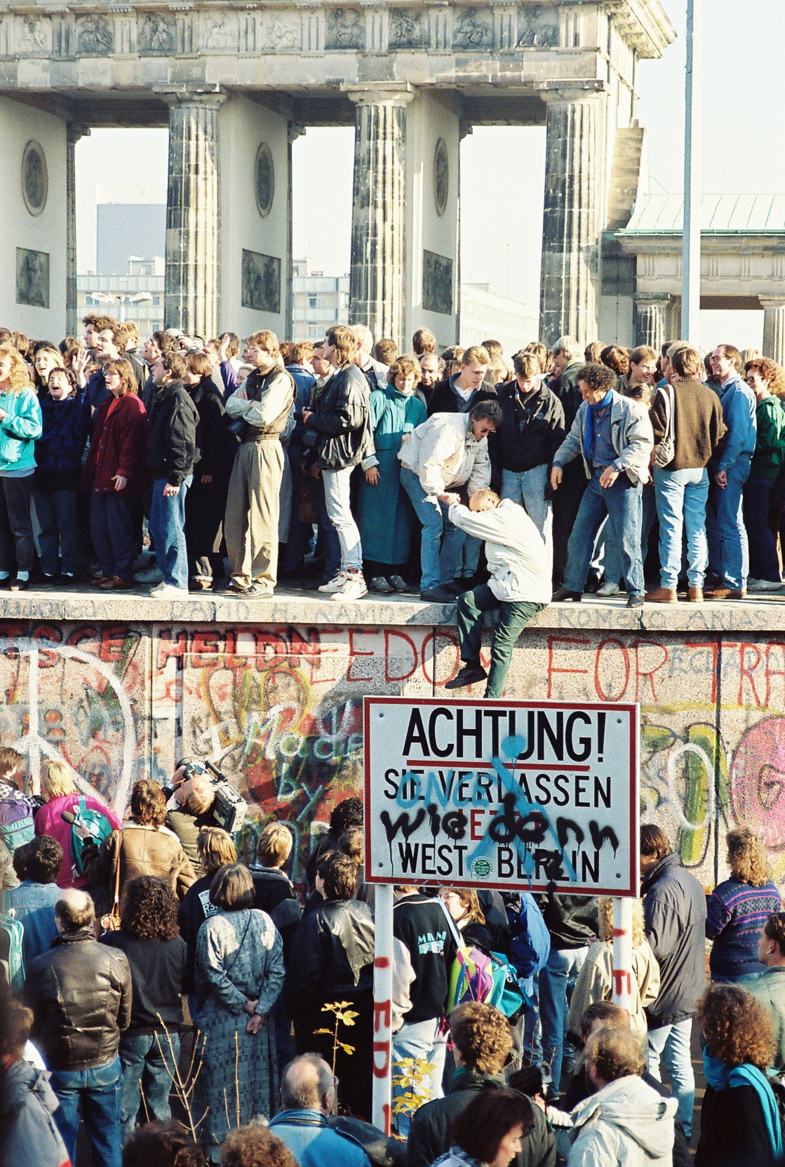 "People atop the Berlin Wall near the Brandenburg Gate on 9 November 1989. A street sign reads ""Achtung! Sie verlassen jetzt West-Berlin"" (""Notice! You are now leaving West Berlin"") has been modified with an additional text ""Wie denn?"" (""How?"")."