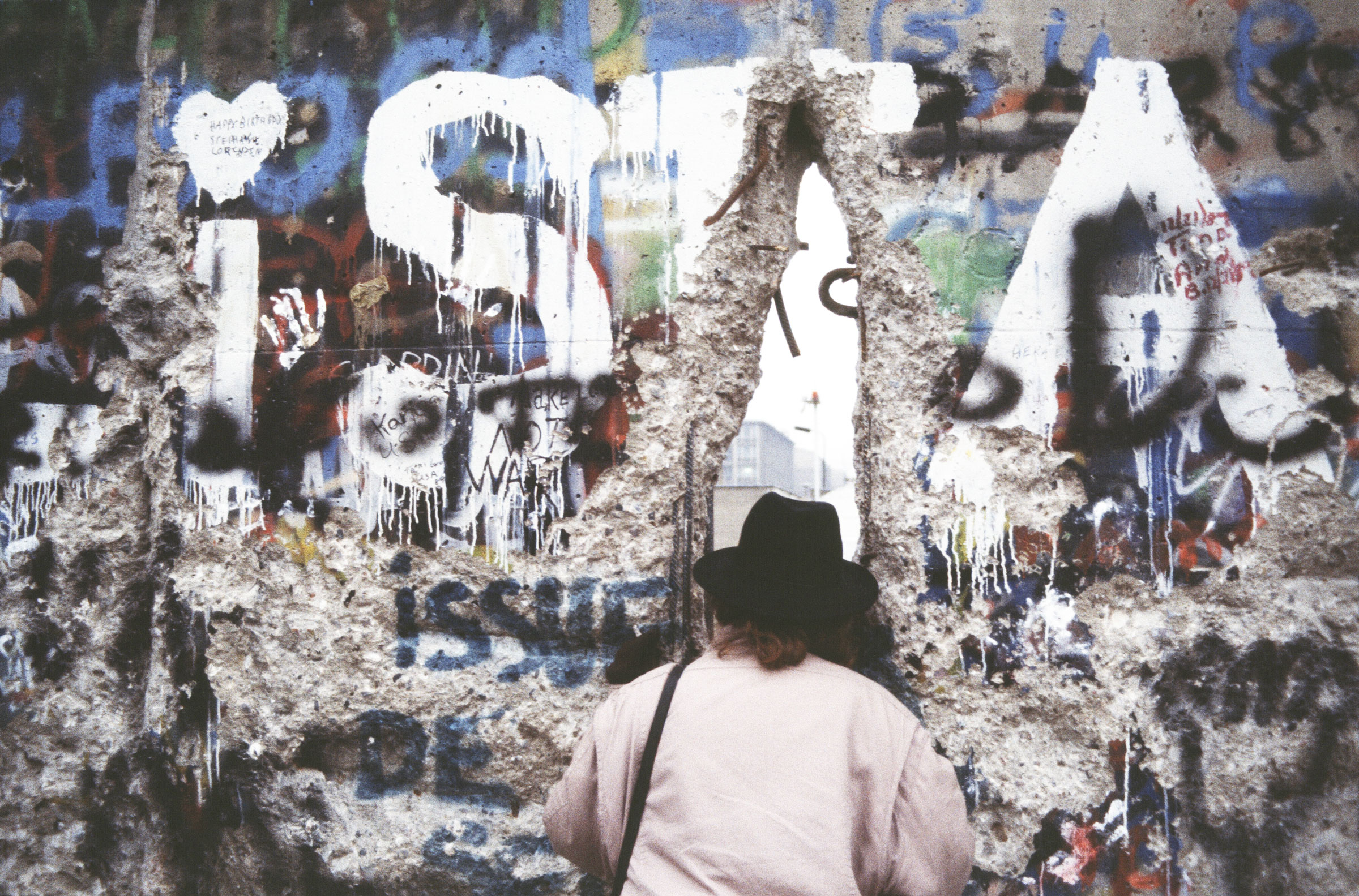 A woman looks through a hole in the Berlin Wall.