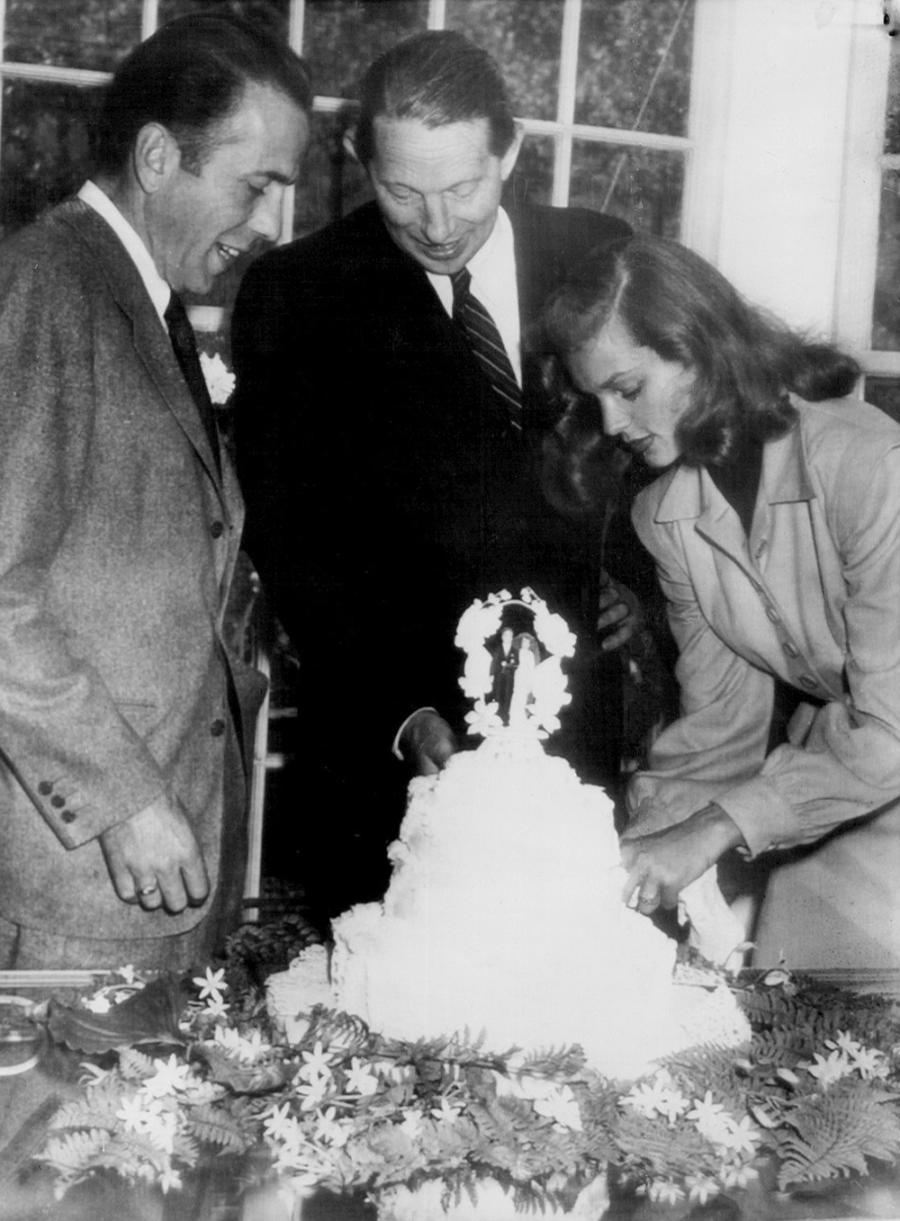 Grouped around their wedding cake are Humphrey Bogart (left), Louis Bromfield, best man, and Lauren Bacall, the bride, 1945. Photograph by the Tucson Daily Citizen. Wikimedia Commons.