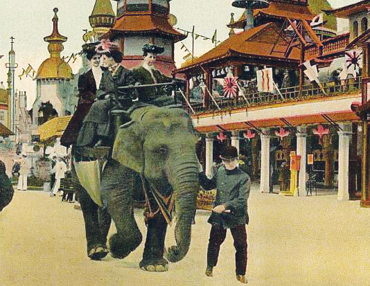 An image from a colorized postcard, showing three women riding on the back of an Elephant, being led by a young man. They are passing by a palatial structure decorated with flags.