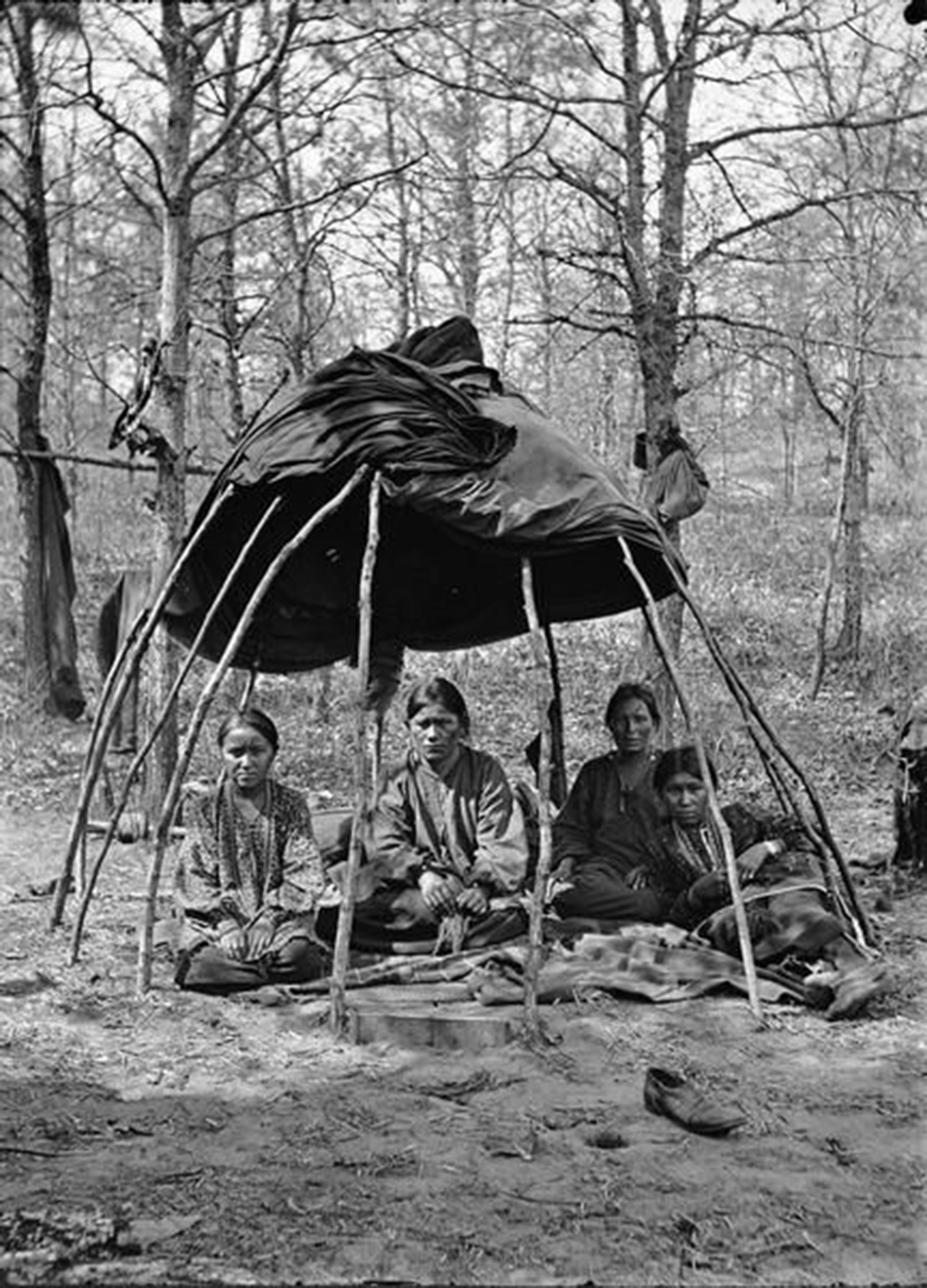 Winnebago women sitting in a chipoteke, a wigwam-like traditional structure. Photograph by Henry Hamilton Bennett. Wisconsin Historical Society.