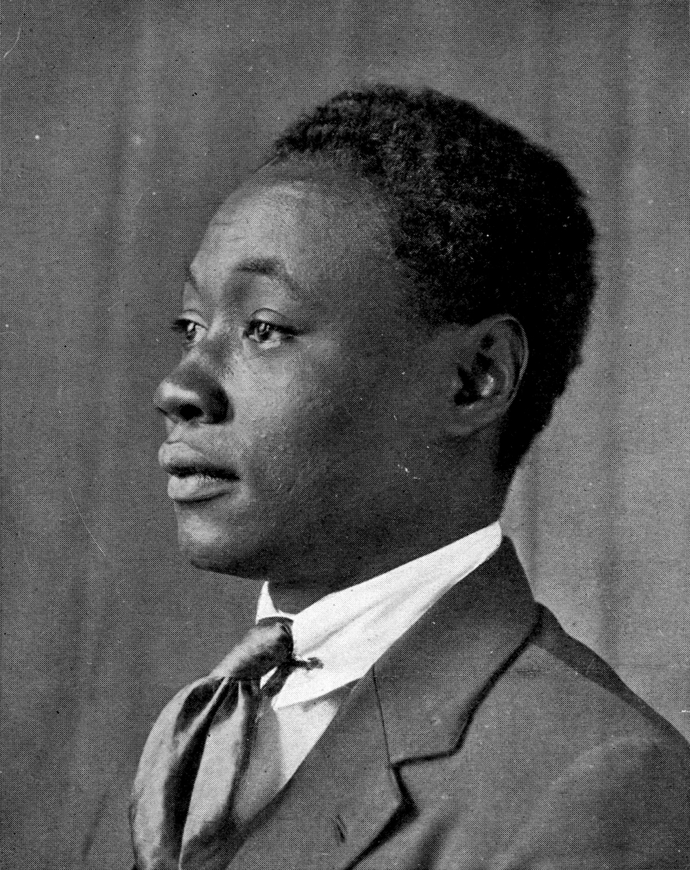 A photograph of a young Claude McKay in 1920. He is in profile, wearing a suit and tie.