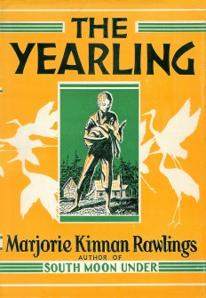 Book cover for The Yearling. A yellow background with black text. A green rectangle in the center of the cover shows a drawing of a young boy holding a fawn, a farm house, and trees in the distant background.