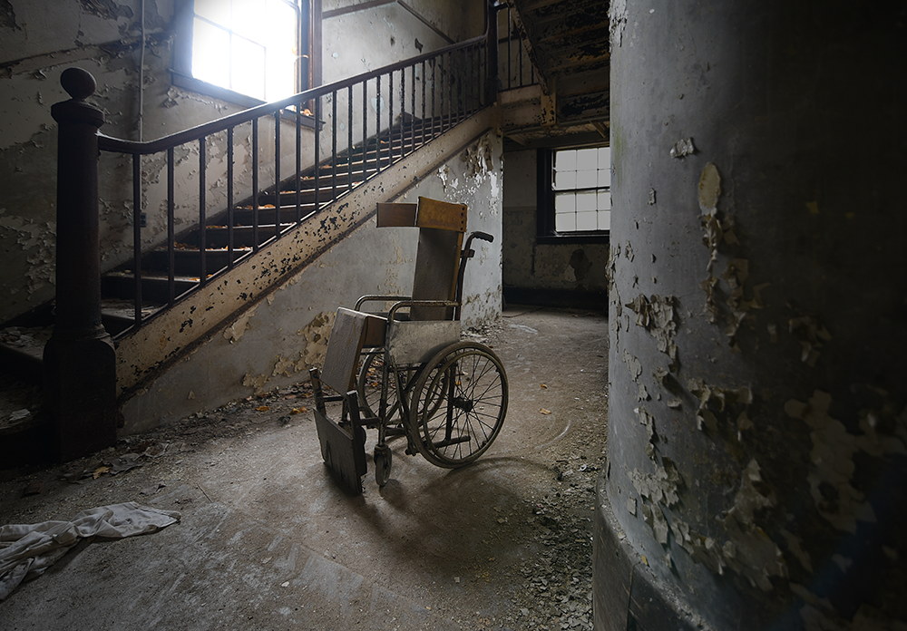 A wheelchair sits at the foot of the stairs in the Fernald's West Building, 2016. The oldest building constructed at the site, it opened in 1890. Photograph by David Whitemyer.