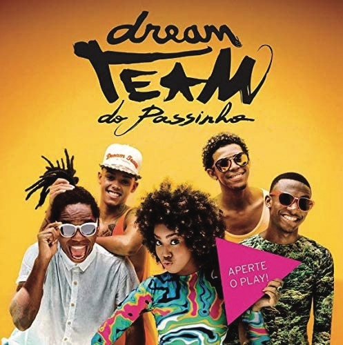 A photograph of Dream Team do Passinho standing in front of a yellow background, with their band name in large letters above their heads
