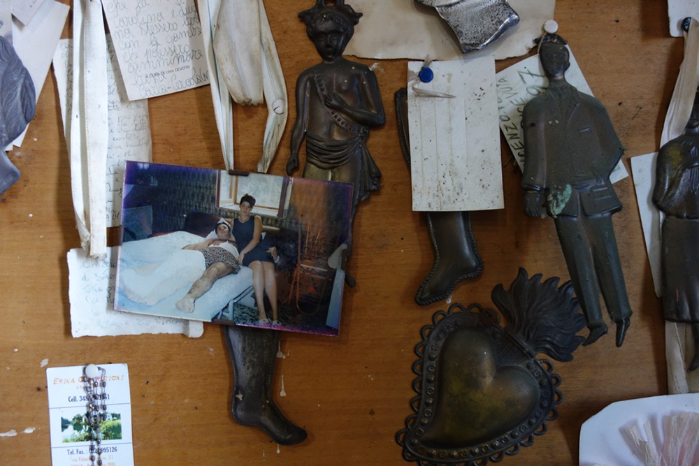 Ex votos, photograph, and notes at the shrine of Uncle Vincent. Photograph by Elizabeth Harper.