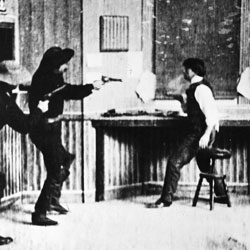 A still from a black and white film showing two people with guns drawn on a third man.