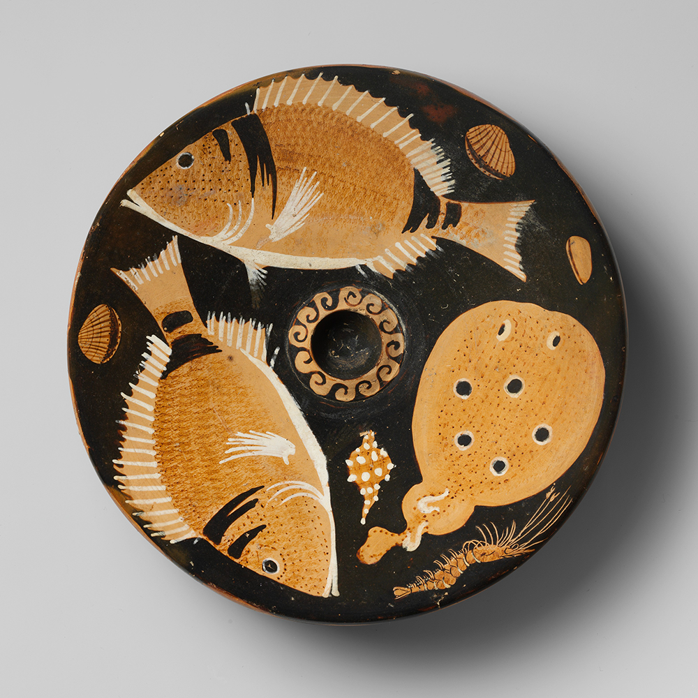Two bream and a torpedo fish are in the center of this terra-cotta fish plate, with two scallops, a mussel, murex, and shrimp in the background, attributed to the Helgoland Painter, c. 350-325 BC. The Metropolitan Museum of Art, Rogers Fund, 1906.