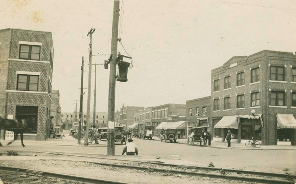 A black and white photograph of the Greenwood district in Tulsa, OK. Depicted are cars parked on a street, a horse, a carriage, people walking along shopfronts, and telephone poles.