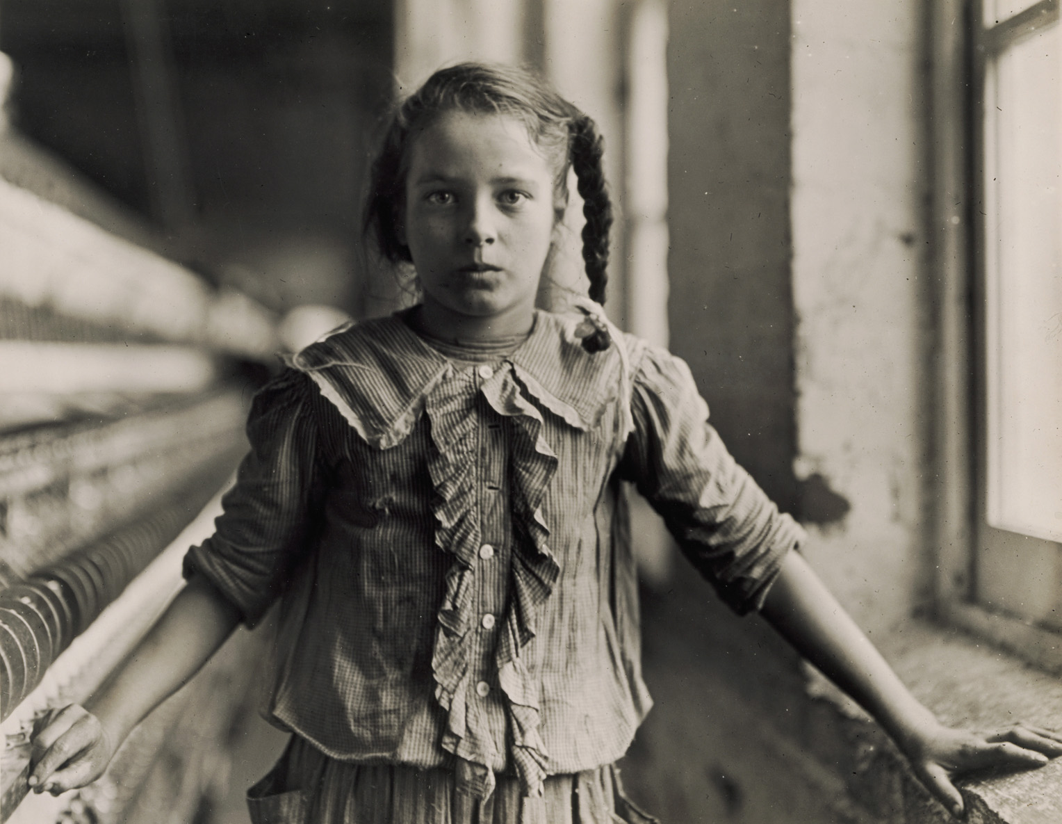 Back and white photograph of a young girl working in a factory in 1908.