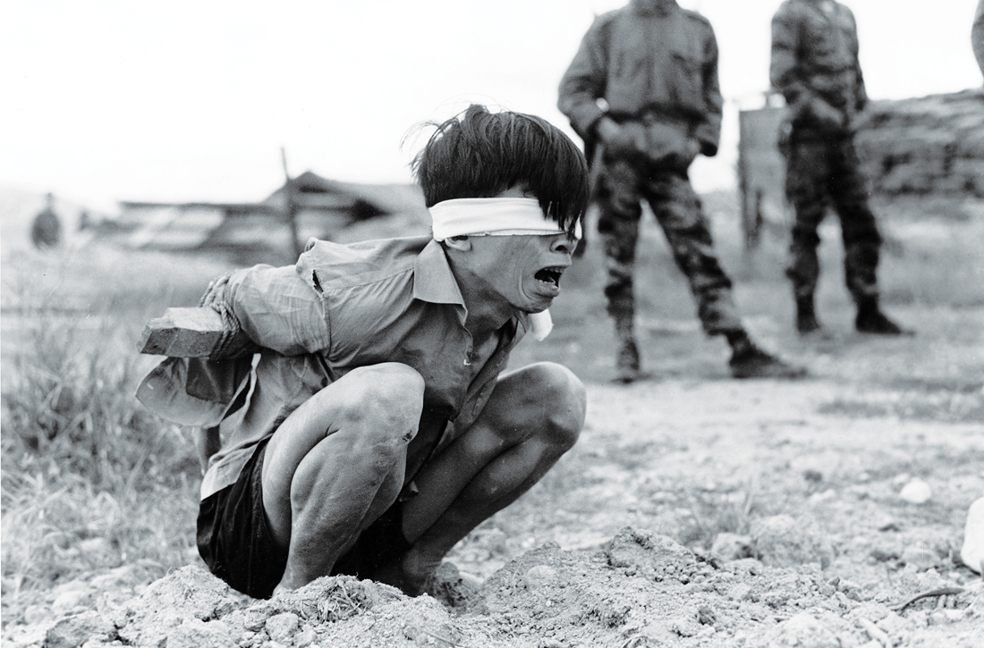 A Vietcong prisoner awaits interrogation at the A-109 Special Forces detachment at Thuong Duc, January 23, 1967. United States National Archives and Records Administration.