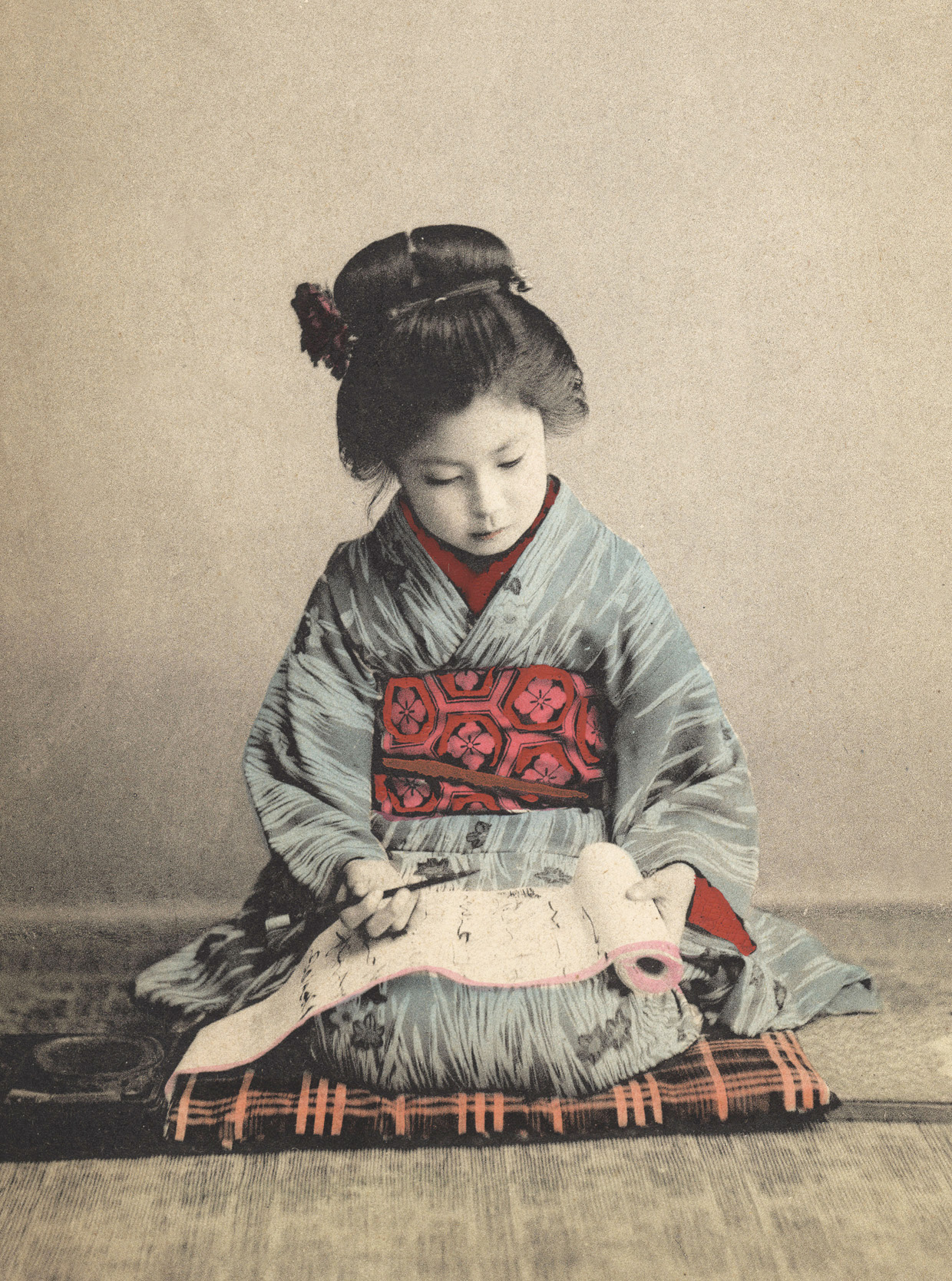 Japanese girl practicing calligraphy, c. 1890.