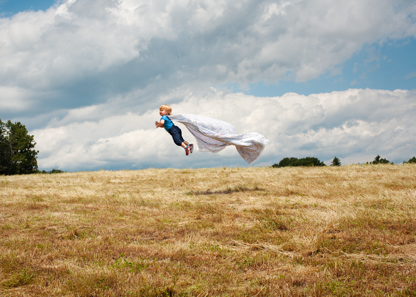 Color photograph of a toddler wearing a cape and seemingly flying in a wheat field.