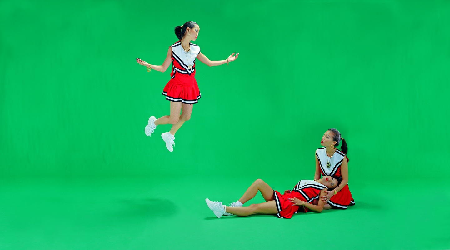 Color photograph of three cheerleaders against a green screen.