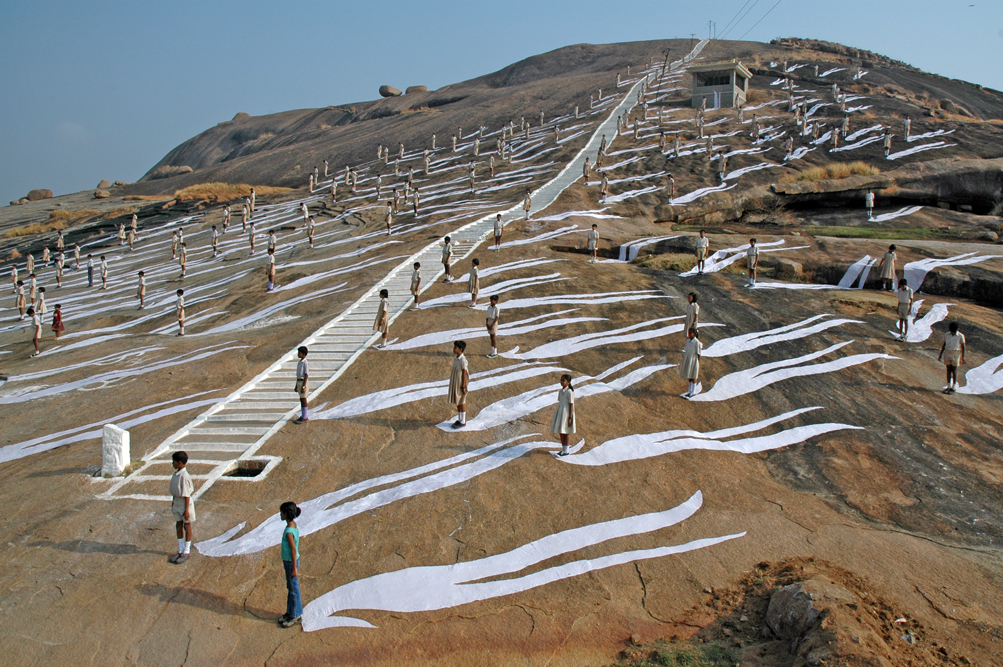 Color photograph of children standing on a hill with long white shadows trailing behind them.
