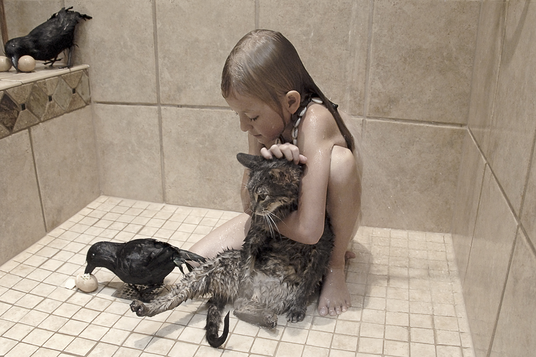 Color photograph of a young girl sitting in a shower with a wet cat and several crows.