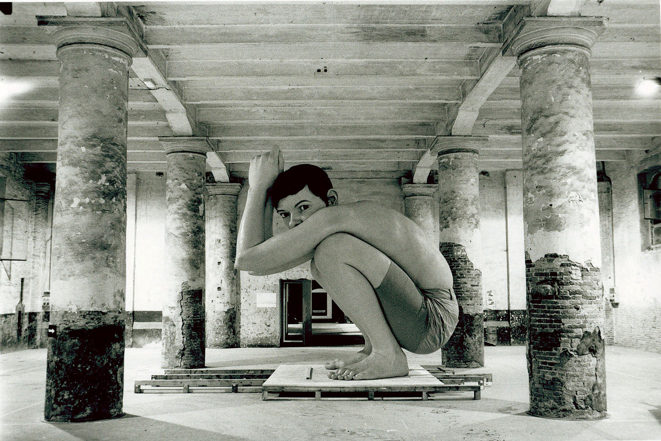 Photograph of a massive realistic sculpture of a young boy crouching down.