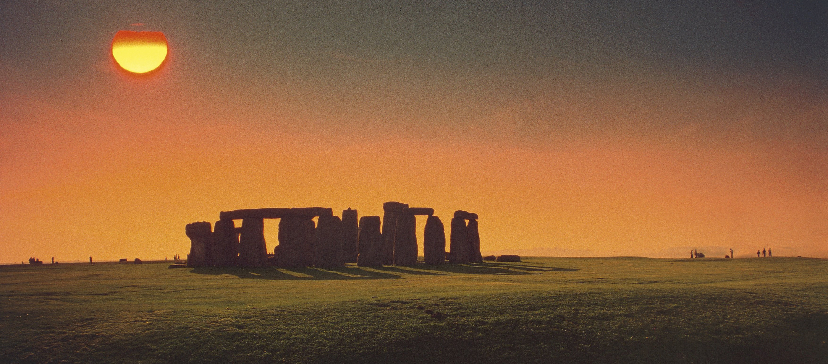 Color photograph of Stonehenge at sunset.