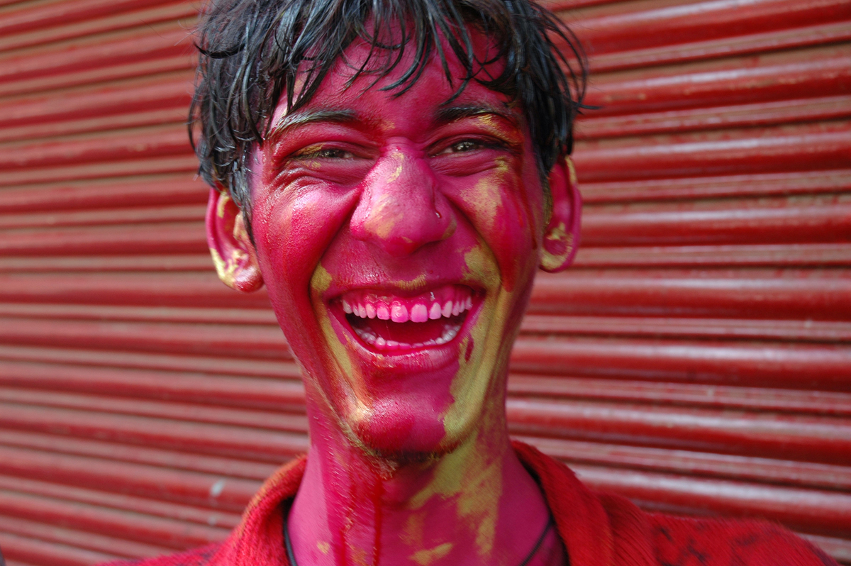 Young man with painted face laughing during Holi festival