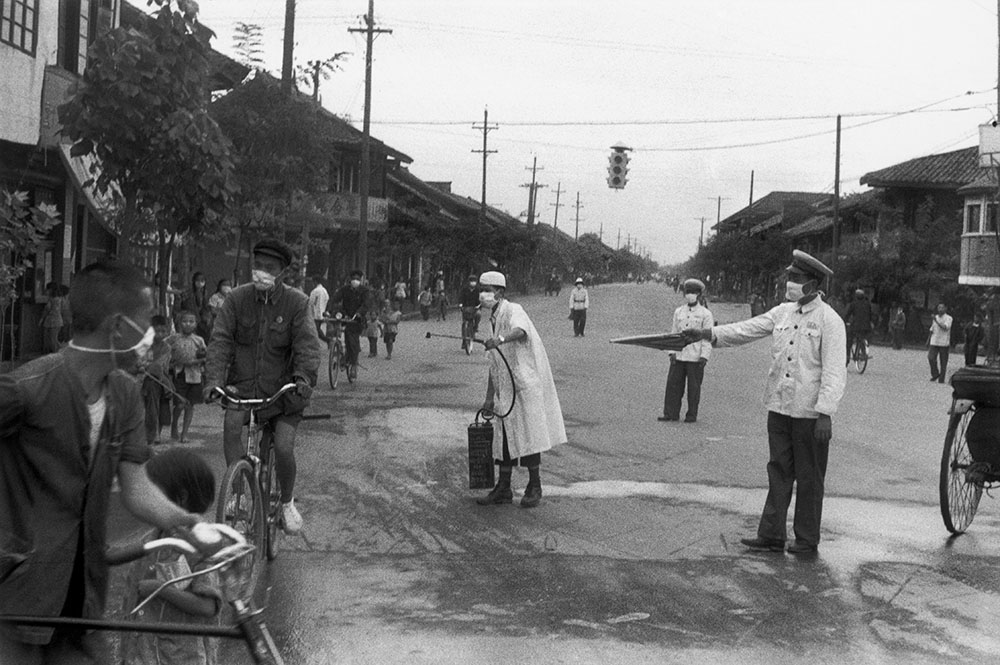 Nurse spraying disinfectant during an epidemic, Chengdu, China, 1958. Photograph by Henri Cartier-Bresson.