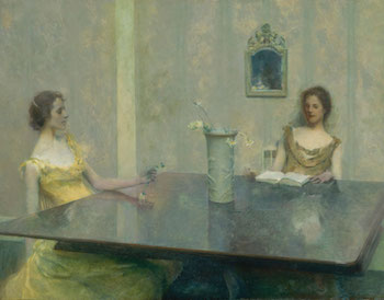 Two women reading at a large table.