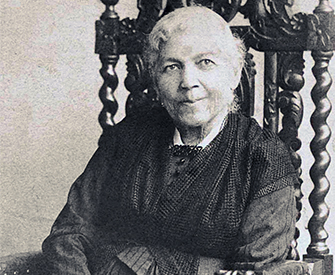 A photograph of Harriet Jacobs, seated in a chair, smiling