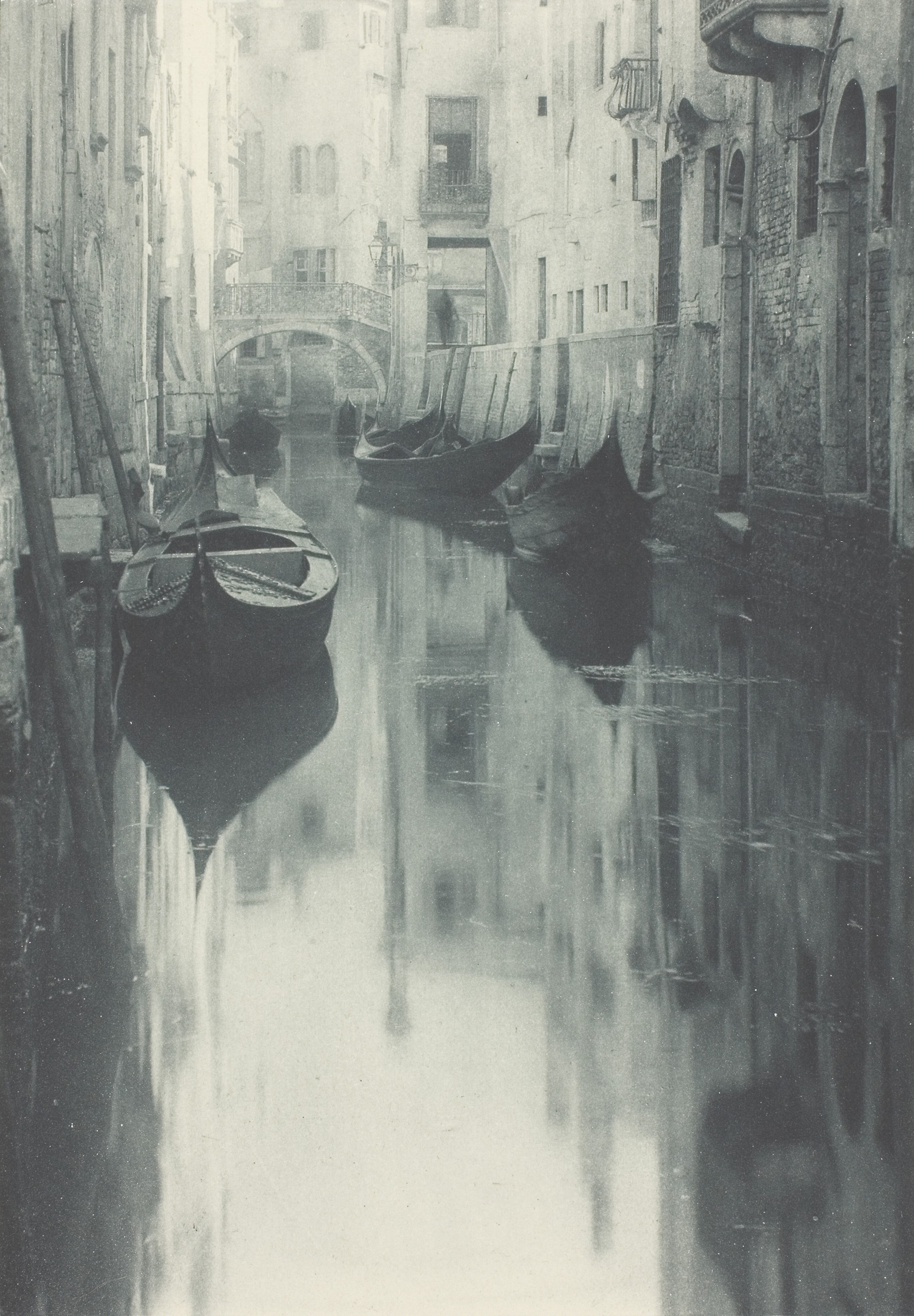 A photograph of empty boats on a Venice canal. In the canal you can see the reflection of the surrounding buildings and the boats.
