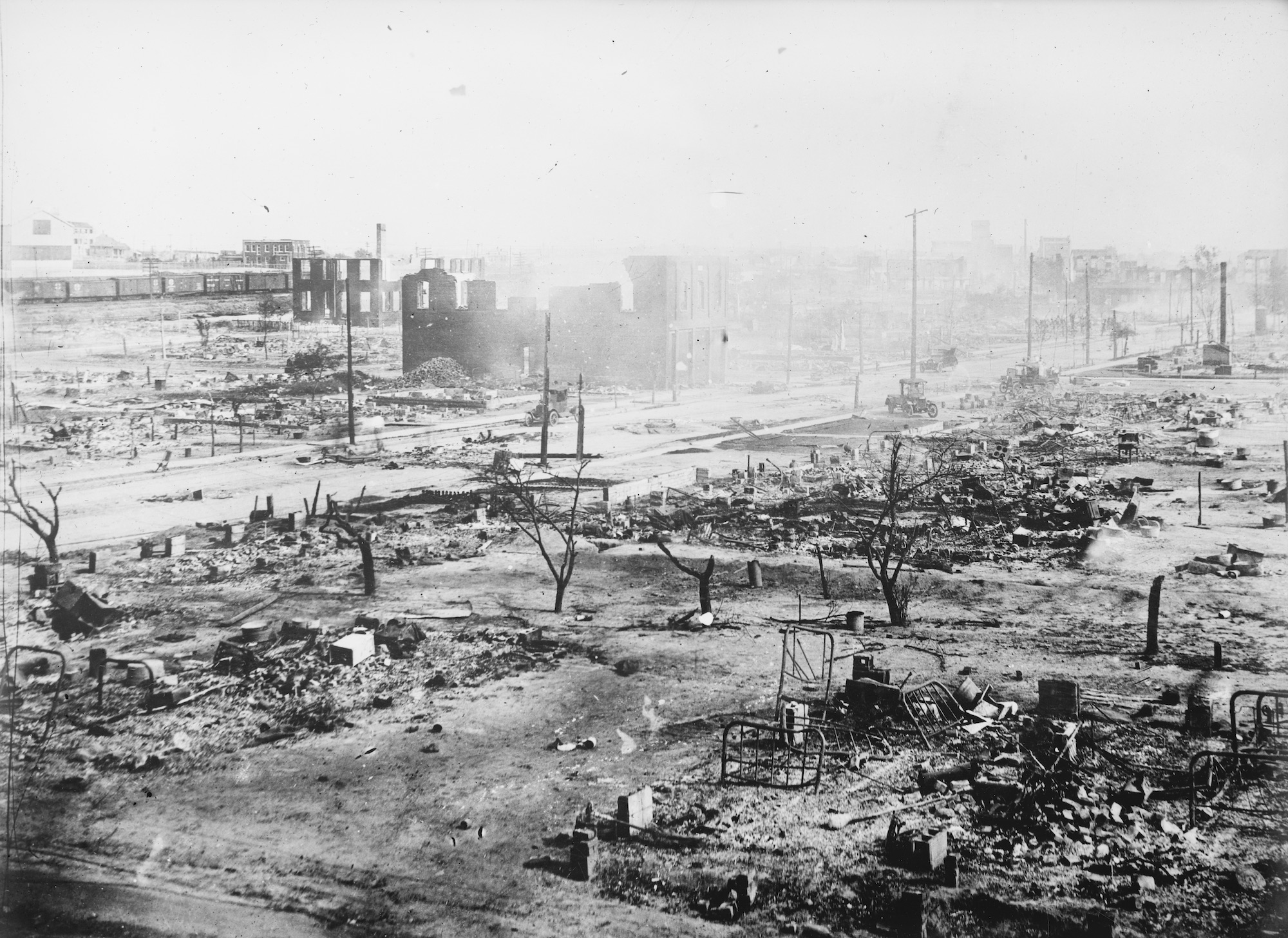 A photograph of Greenwood, Tulsa after the 1921 race massacre. Most of the buildings have been completely destroyed—burned to the ground—others are severely damaged. The air looks hazy with smoke, and you can see burnt remains of bed frames in the rubble.