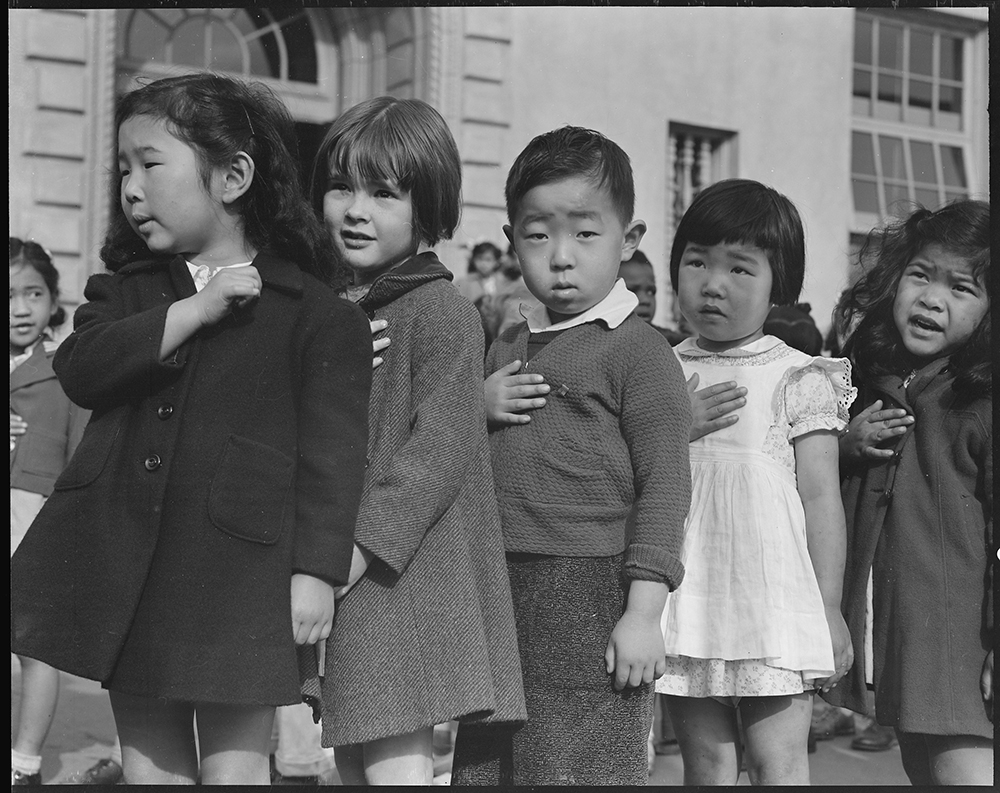 Many children of Japanese ancestry attended Raphael Weill Public School in San Francisco prior to evacuation. This scene shows first graders during flag pledge ceremony, 1942. Photograph by Dorothea Lange. National Archives at College Park.