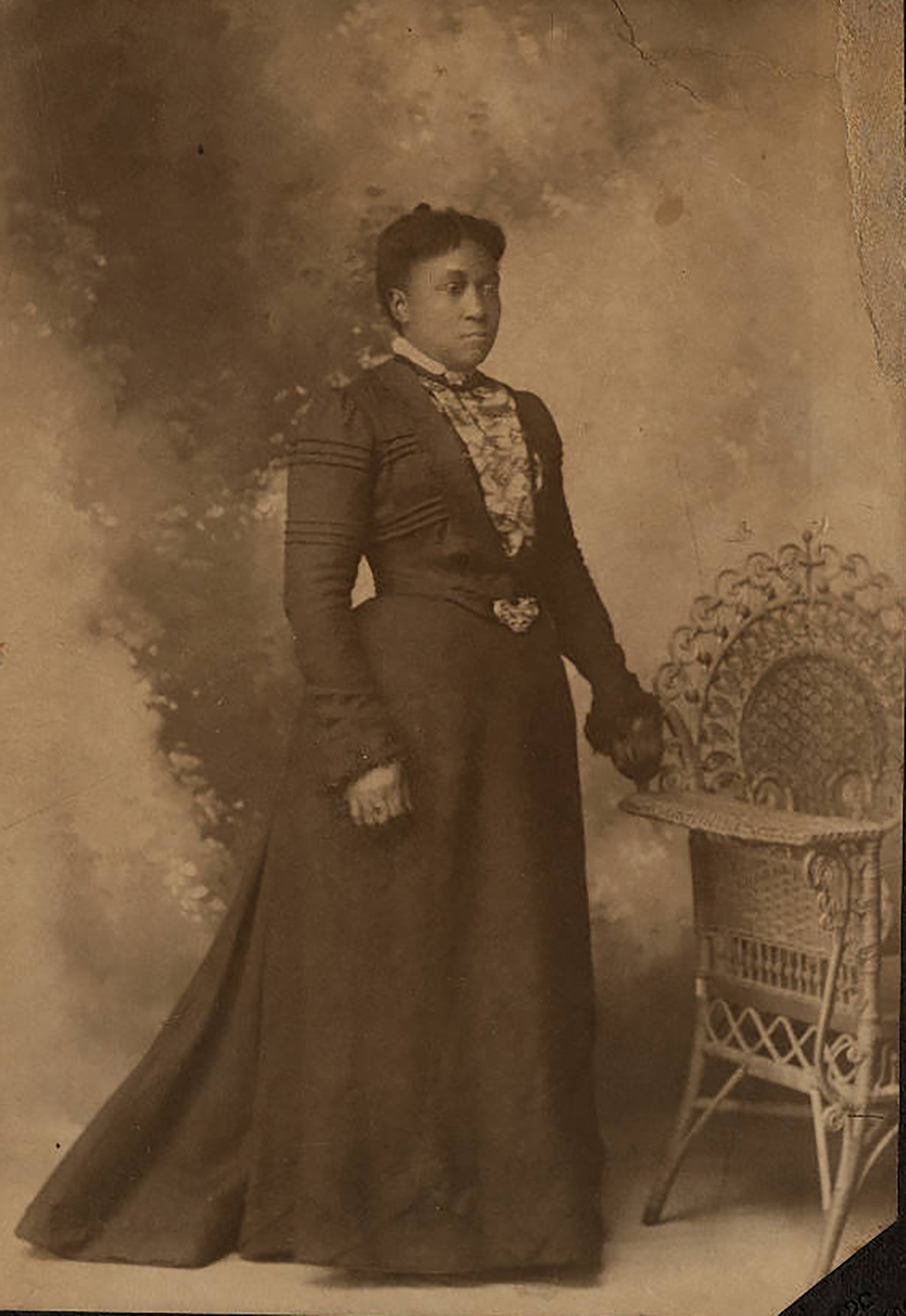 Dr. Wiley's hair is parted and pulled back. Standing in a high-collared, long dress, she appears solemn and confident. Her left hand rests on an ornate wicker chair. Caroline Still [Wiley] Anderson, c. 1880. Photograph by J.A. Hurst. William Still Collection.