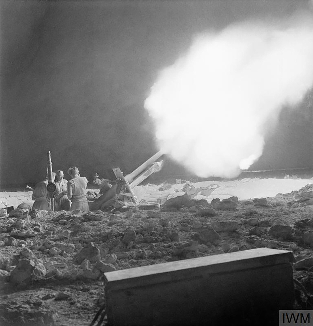British 25-pounder guns fire at Erwin Rommel's Afrika Korps on the night of June 2, 1942, during the Battle of Gazala. Photograph by William George Vanderson. © Imperial War Museums.