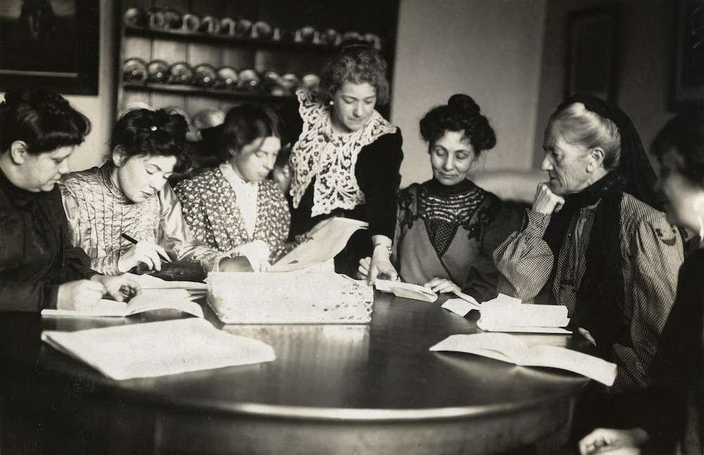 Black and white photograph of Flora Drummond, Christabel Pankhurst, Jessie Kenney, Nellie Martel, Emmeline Pankhurst, and Charlotte Despard working around a kitchen table.