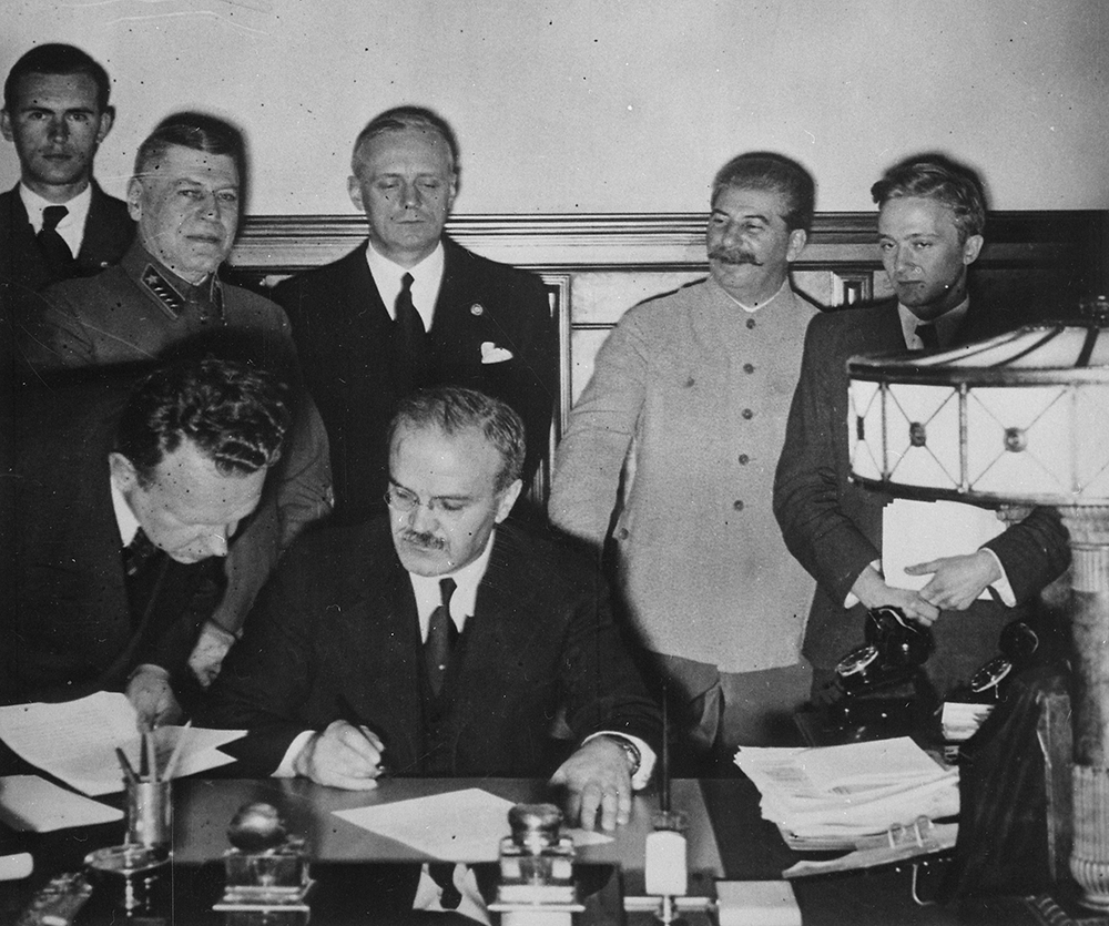 Soviet foreign minister Vyacheslav Molotov signs the German-Soviet Boundary and Friendship Treaty; Joachim von Ribbentrop and Joseph Stalin stand behind him, Moscow, September 28, 1939. U.S. National Archives and Records Administration.