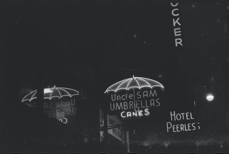 A black-and-white photograph of a neon sign shaped like an umbrella and the words uncle sam umbrellas canes.