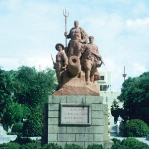 a photograph of a monument depicting three men standing over a cannon. One holds a trident.