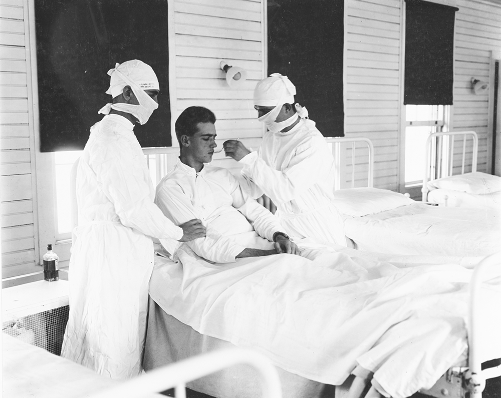 Masked medical personnel giving treatment to an influenza patient at a U.S. Naval Hospital, New Orleans, 1918. U.S. Naval History and Heritage Command.