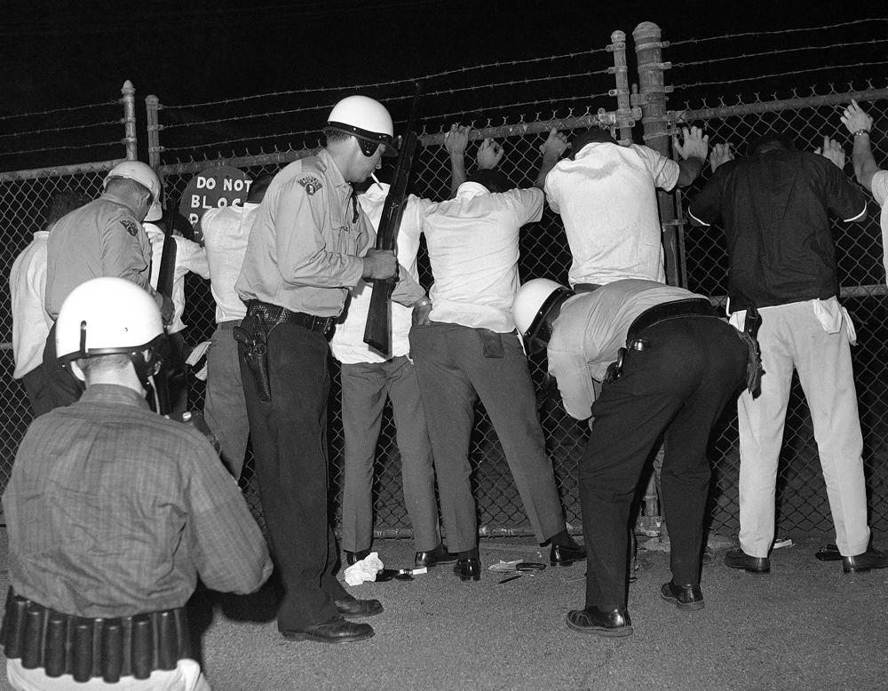 Police search youths in riot area of Cleveland, July 23, 1966 as trouble continued for a fifth night with reports of shooting and minor incidents, AP Photo/Charles Knoblock.