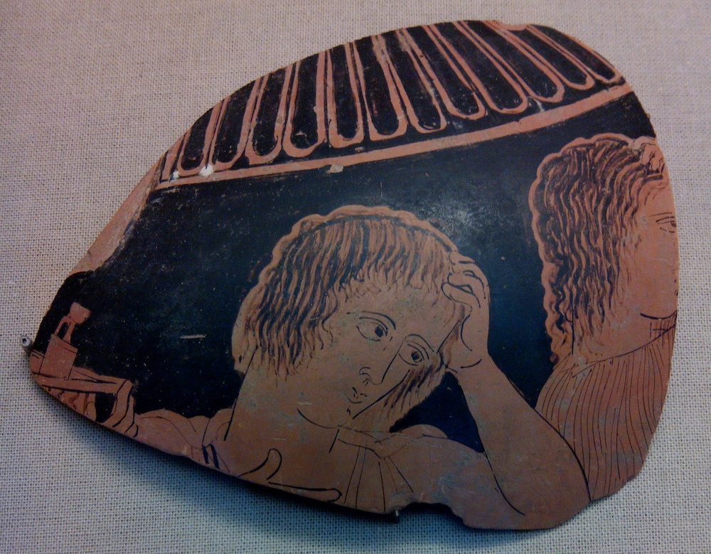 A piece of greek pottery showing a figure in mourning. The person is depicted with a hand on their heart, and holding their head in their other hand.
