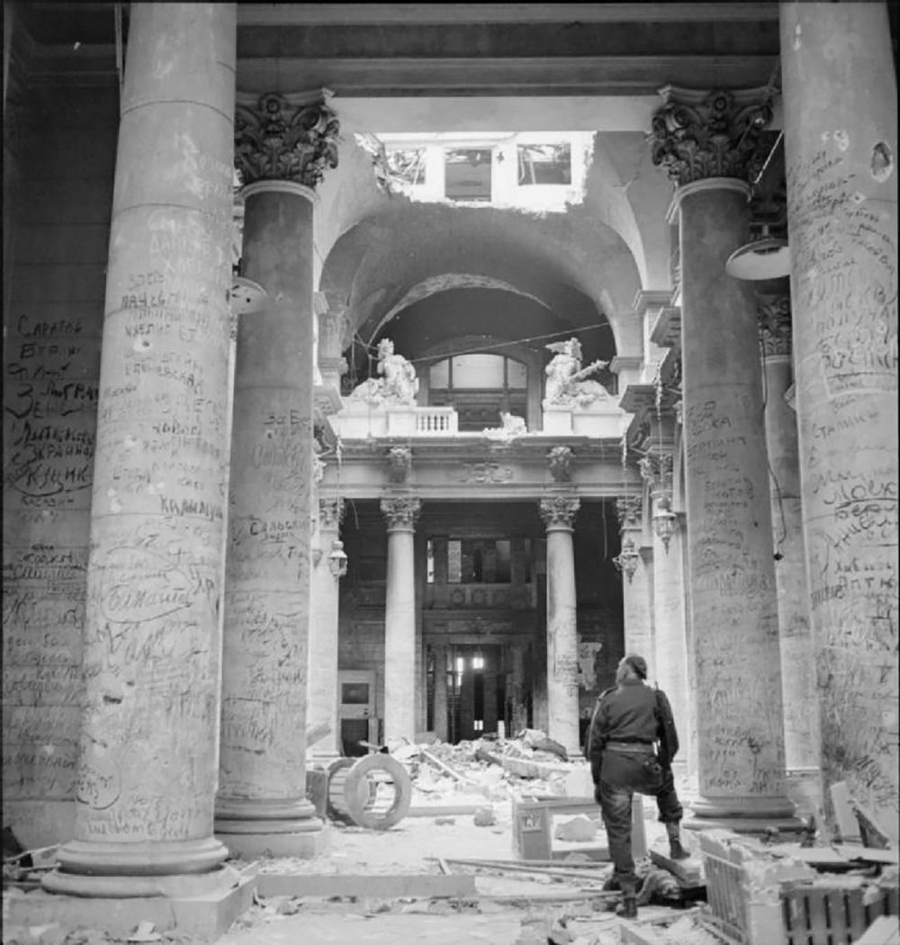 A British soldier stands among the ruins of the German Reichstag in Berlin, looking at pillars covered in graffiti left by Soviet soldiers, 1945. Wikimedia Commons, Imperial War Museums.