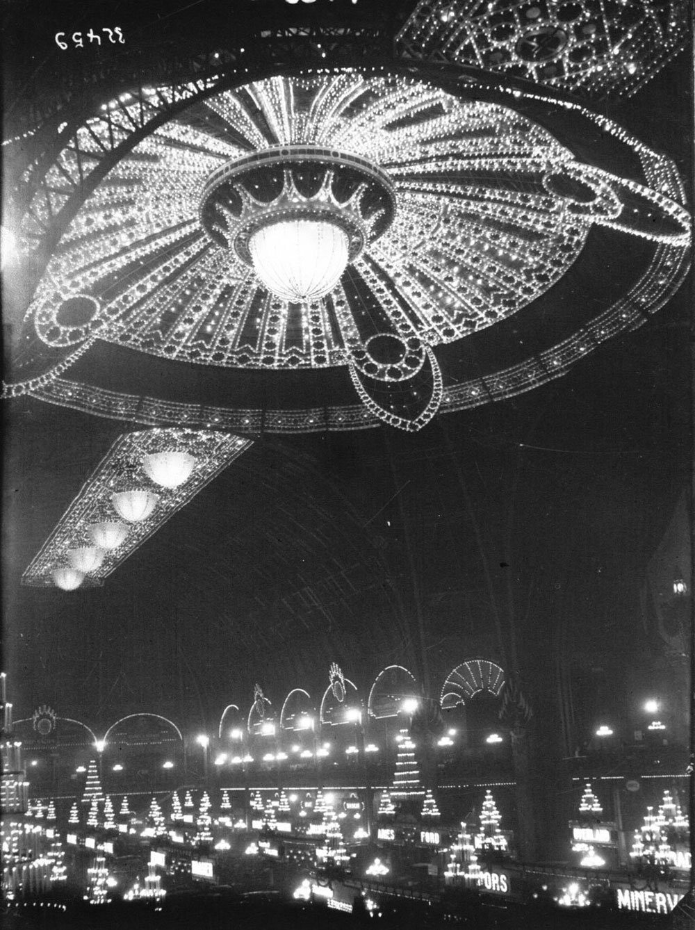 A black-and-white photograph of a large room with high ceilings. The ceiling is decorated with an ornate lighting design.