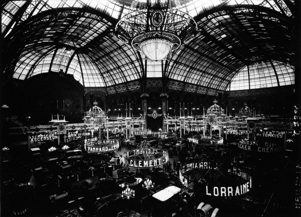 A black-and-white photograph of a large room with a domed glass ceiling. The room is full of cars, and lights above the cars spell out the names of car manufacturers.