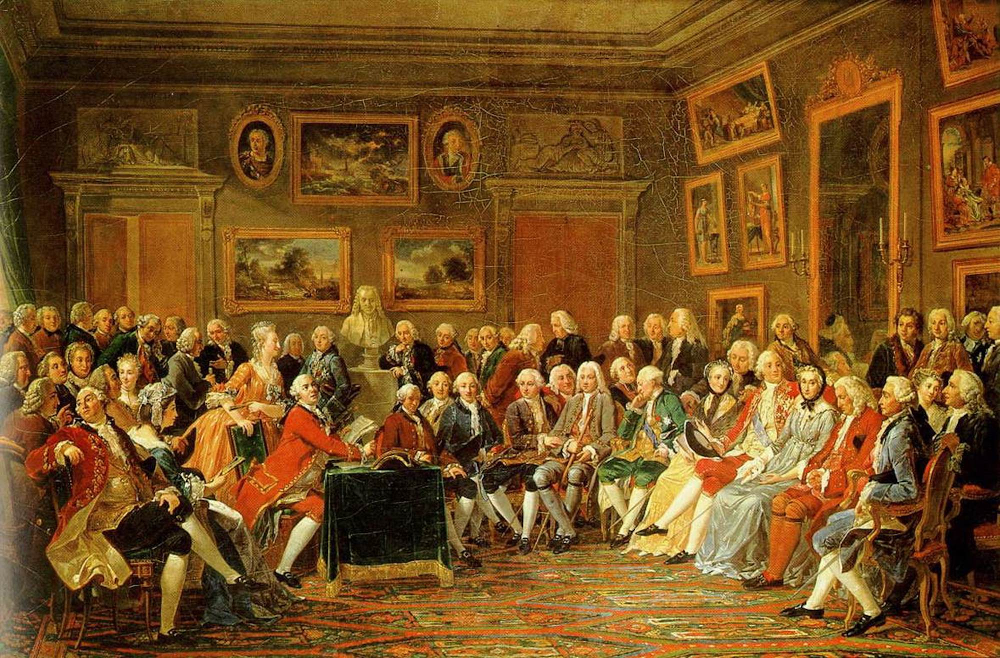 A painting of a large drawing room filled with people seated around a central figure giving a reading. While most in the room are men, some women are present. The room is very large, with high ceilings, and the walls are covered in paintings.