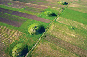 A photograph of Scythian burial mounds. Large green mounds in a field, seen from above.