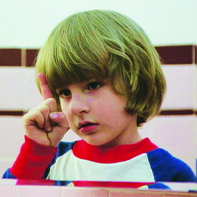 A little boy staring at his bent index finger