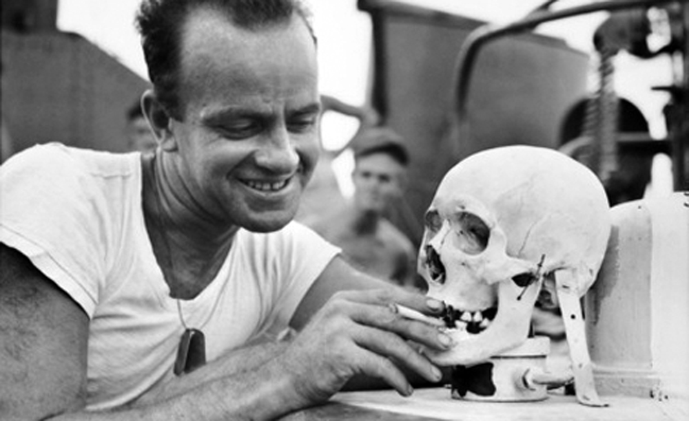 Lieutenant with Japanese skull used as a mascot aboard a Navy torpedo boat, 1944.